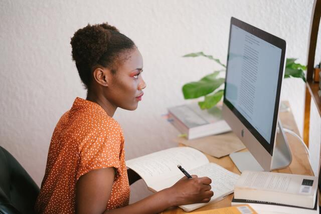 Cómo estudiar a distancia por internet. Chica estudiante toma apuntes delante de su ordenador.