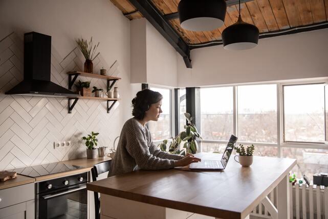 Estudiar a distancia tiene el mismo valor que presencial. Persona estudiando a distancia desde su cocina.