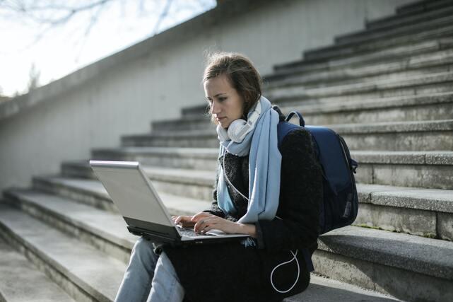 Estrategias para estudiar a distancia. Chica estudiando frente al ordenador sentada en la calle.