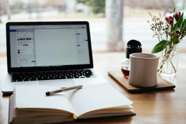 Estudiar a distancia desventajas. Mesa preparada para una clase online, con ordenador, libreta, bolígrafo y taza.