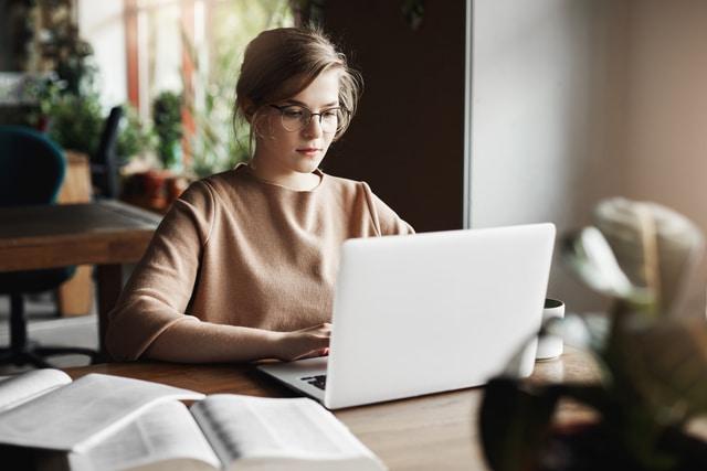 Estudiar a distancia qué es. Chica con gafas sentada frente a su ordenador atendiendo a una clase a distancia.