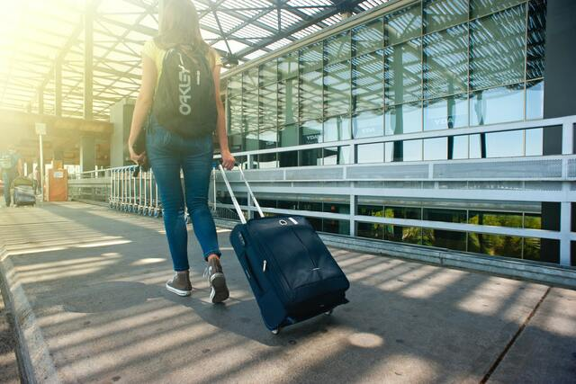 Persona cargando una maleta de camino al aeropuerto para irse a estudiar a distancia desde otro país.