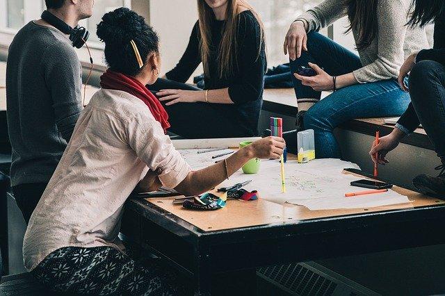 Alumnos estudiando juntos en una clase presencial